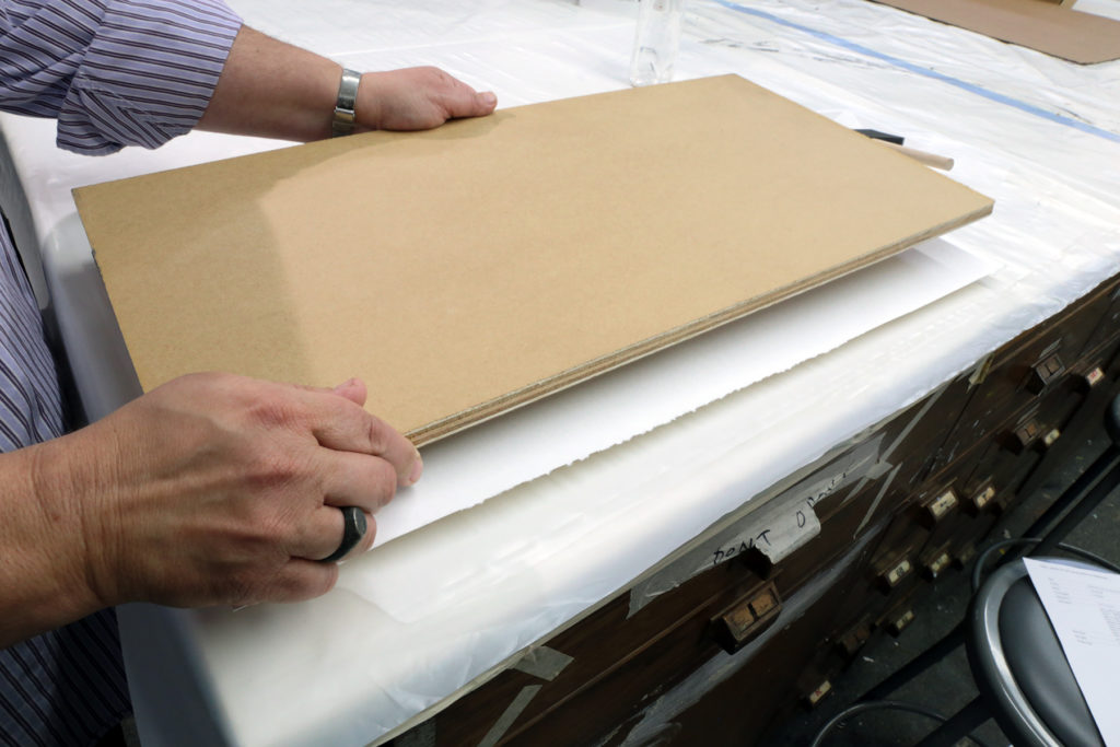 Position the second board on top of the second blotting paper sheet, and place weights on top of the board.