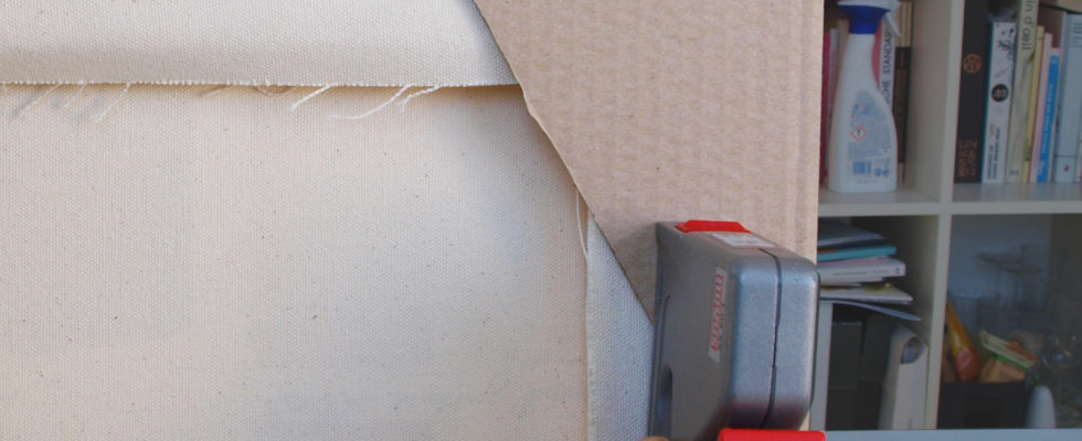 The corner protection is stapled to the reverse of a canvas painting.
