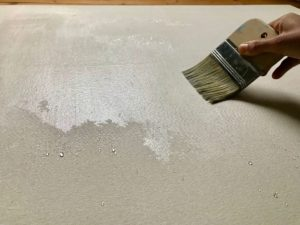 a stretched cotton duck canvas is being washed with luke warm water, since cold water tends to bead up more.