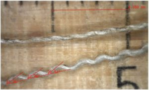Fig. 4: The upper yarn is a weft thread, the lower yarn a wavy warp thread, from a linen canvas.